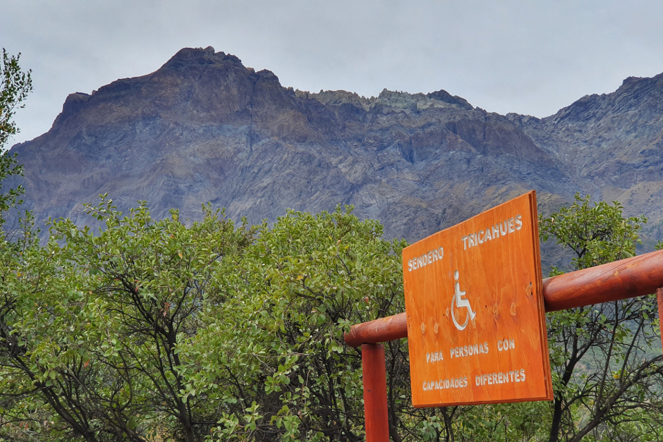 wheelchair accessible walking track sign with mountain peak behind