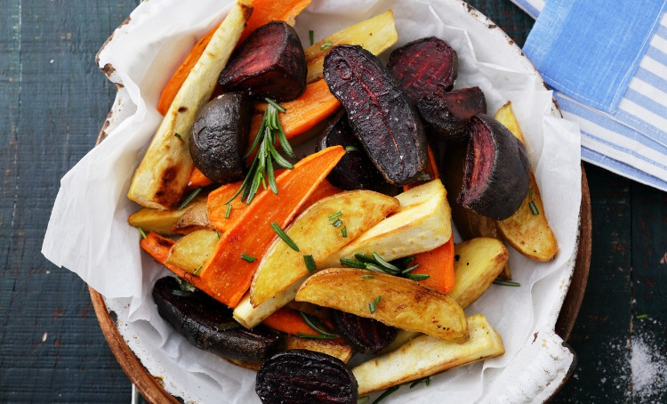 A plate of baked vegetables, carrot, beetroot potato, with some rosemary sprinkled on top.