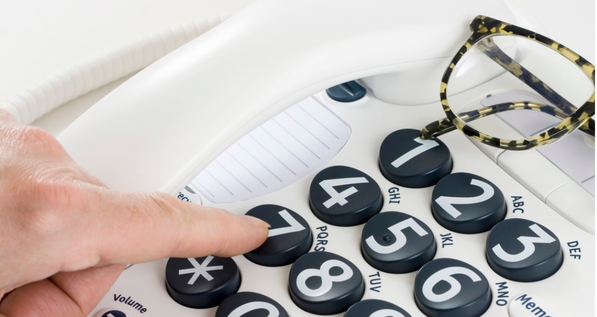 A white landline telephone with large black buttons has number in white. A person is hovering a finger over the buttons. Spectacles can be seen at the top right of the image.