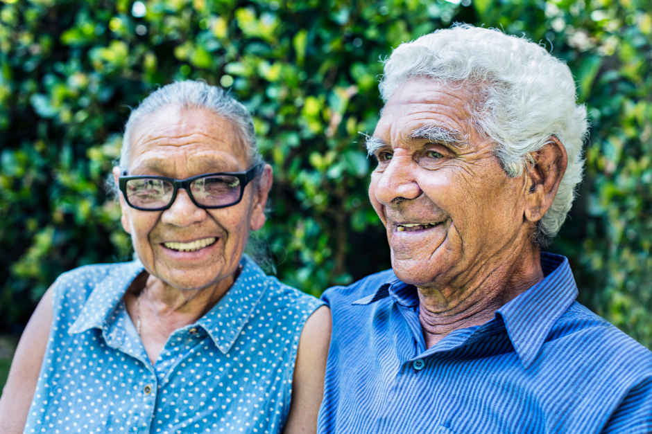 Image of smiling elderly Indigenous couple wearing blue shirts.