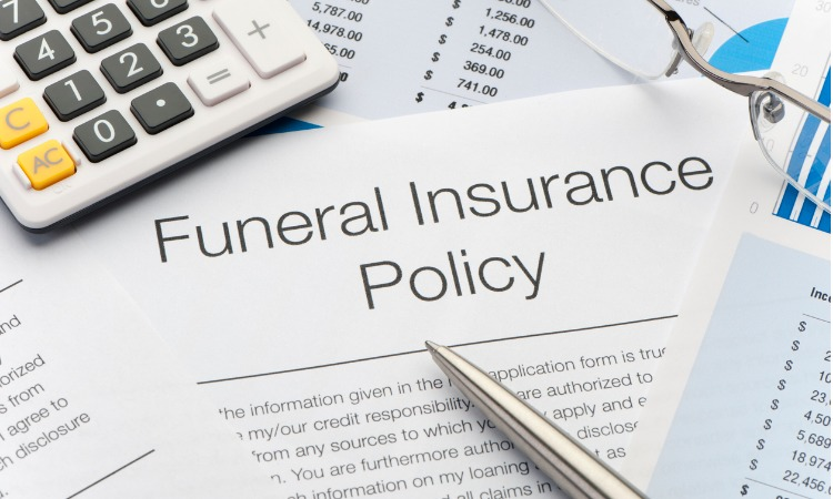 Close up of funeral insurance policy papers, with a silver pen and calculator in the corner.