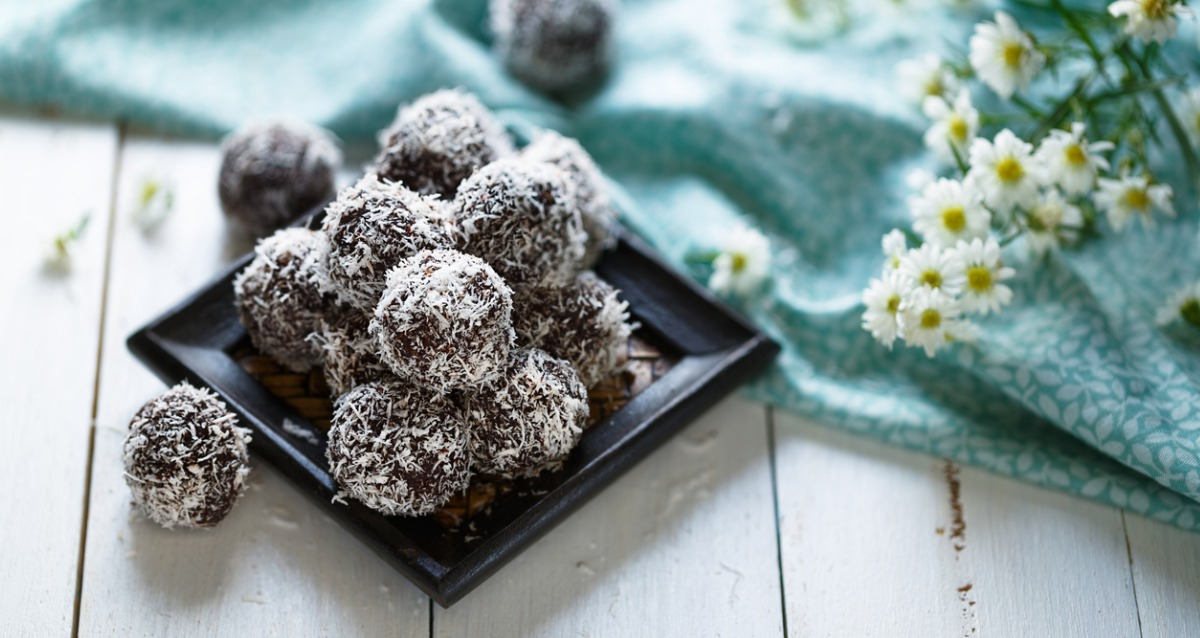 An image of bliss balls stacked on a black plate. They are coated in coconut. A blue floral tablecloth and some flowers are on the right of the photo