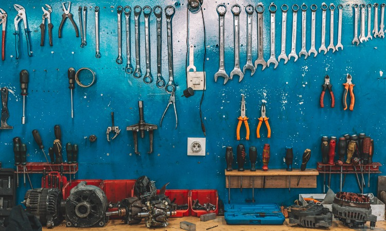 Image of organised tools hanging on a blue wall inside a garage or shed.