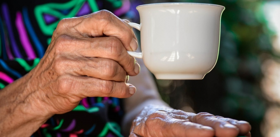 Image of an aged woman's hand holding a white cup