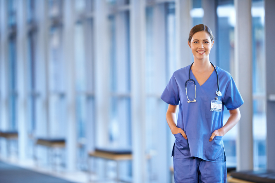 Image of smiling female nurse in blue nurse outfit standing in a hallway.