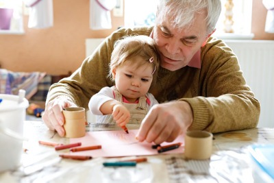 Image of elderly man and little girl colouring in together
