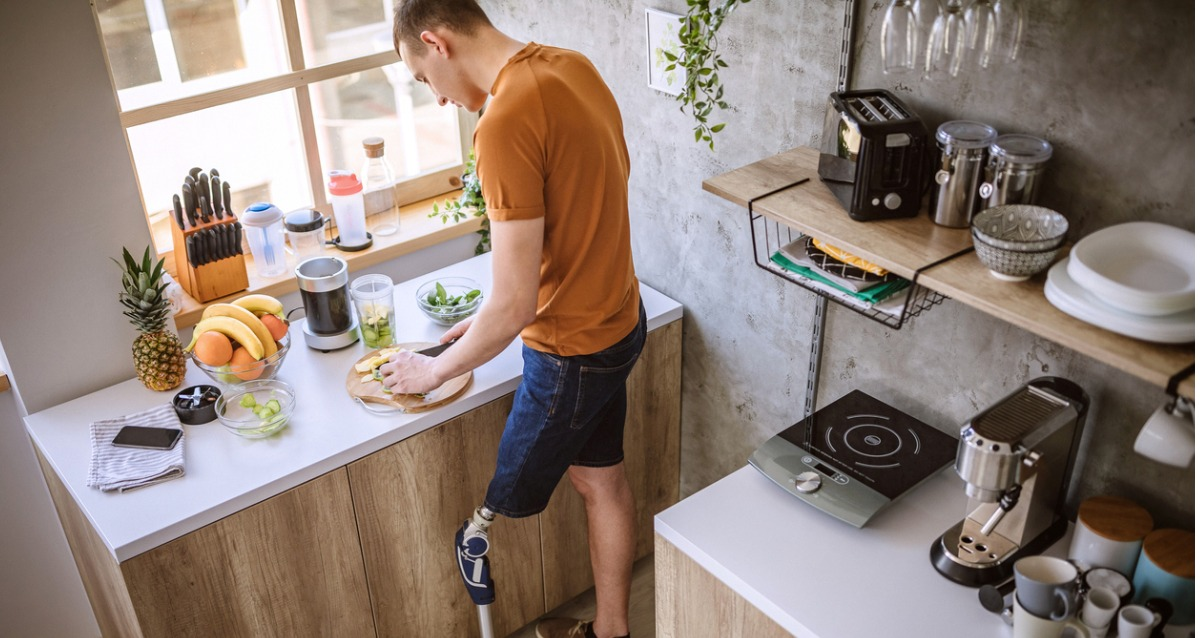 A photograph of a young male with prosthetic leg. He is standing in a kitchen, chopping food. In front of him is a blender to make a smoothie with.