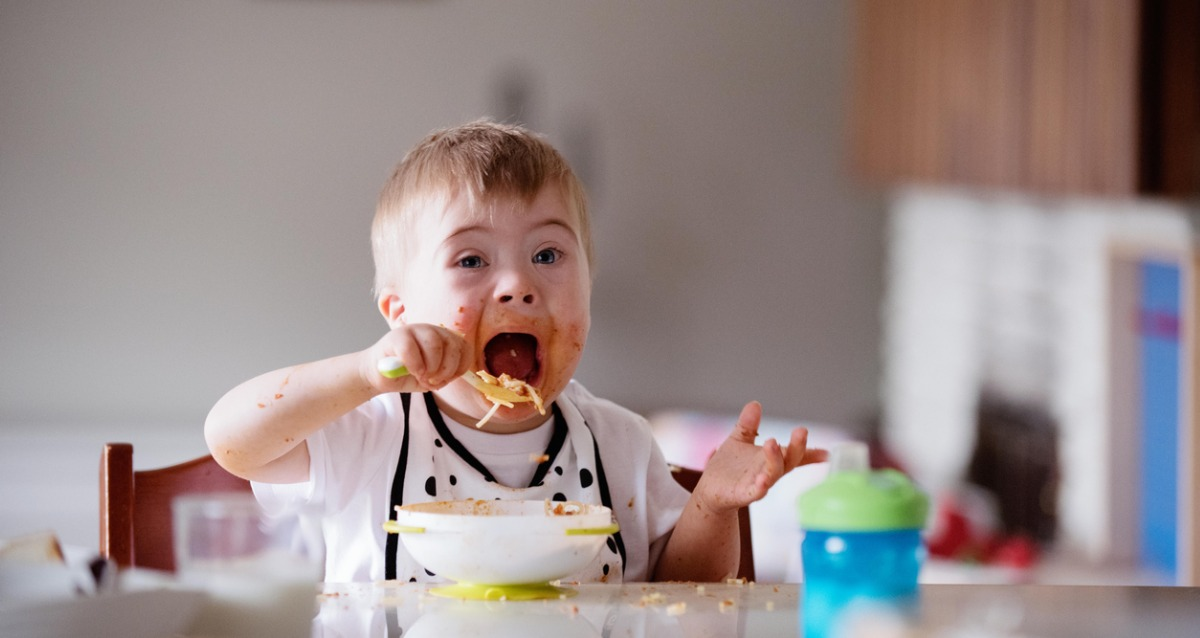 A toddler with disability is sitting in a high chair and feeding himself spaghetti. His cheeks are covered in food and his mouth is open wide to put a spoonful in.