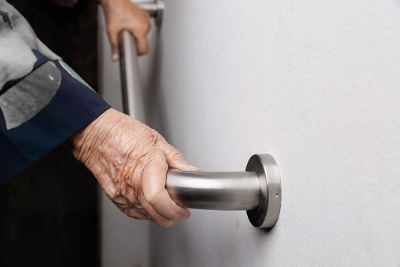 Elderly woman holding onto a grab rail