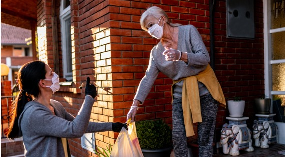 Woman wearing mask and gloves hands a shopping back to an older woman also wearing mask and gloves
