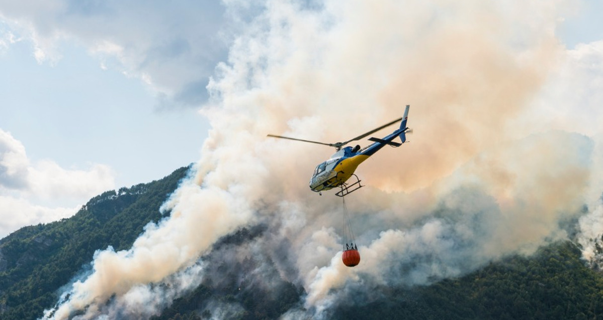 Image of a helicopter carrying a bucket of water near a bushfire.