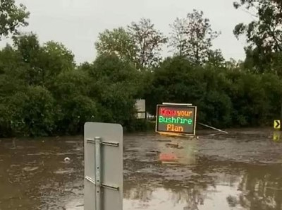 Mobile Bushfire Survival Plan sign inundated by floodwater