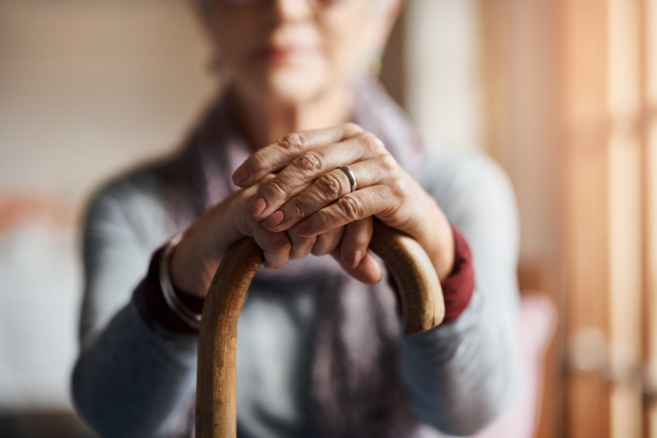 Older woman holding a cane.