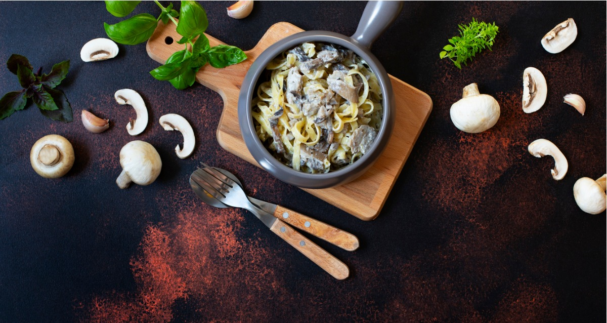 A concept photo of mushroom stroganoff, a dish with mushrooms and pasta, aongside is a knife and spoon. Around the bowl are mushrooms, basil, herbs and paprika.