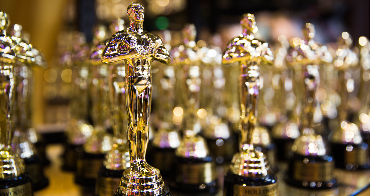 An image of a lineup of Oscar statues from the Academy of  Motion Picture Arts and Sciences.