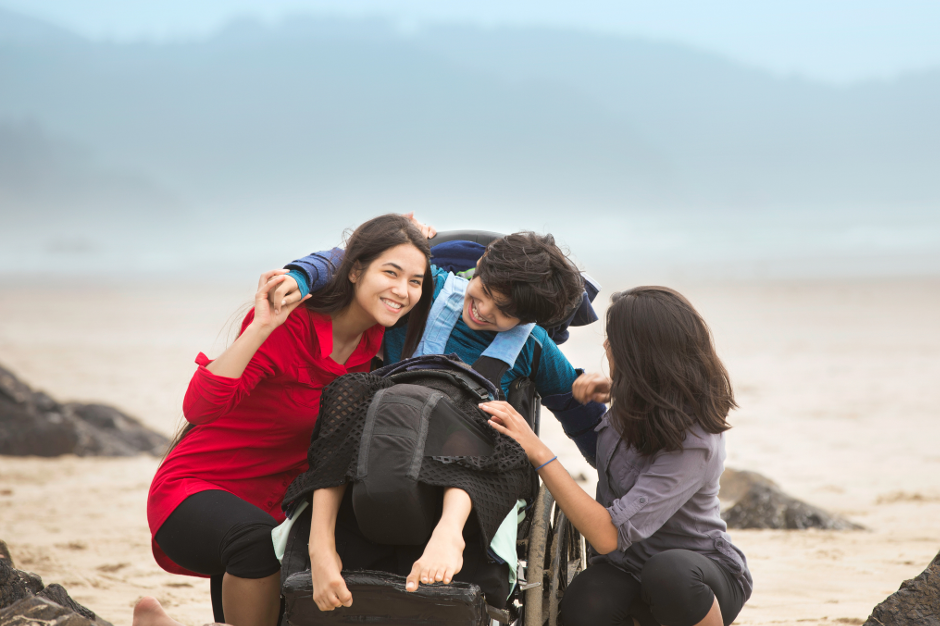 Boy in wheelchair on beach with two companions