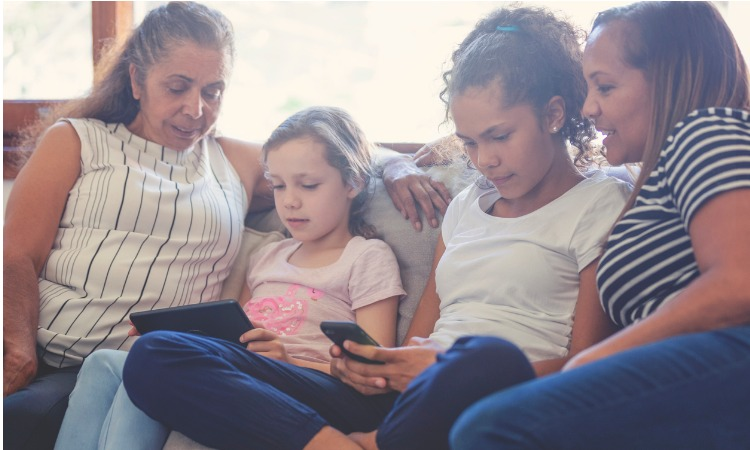 Image of multi-generational Indigenous family sitting on couch with the kids look at a smartphone and tablet device.