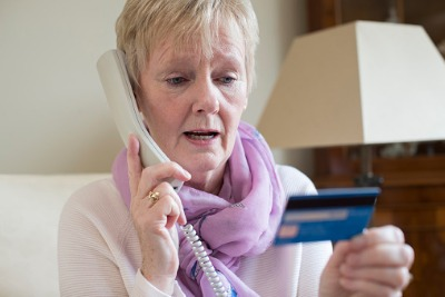 Elderly woman on phone call and holding credit card