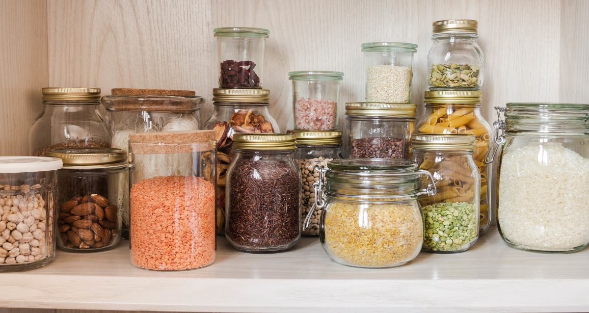 An image of a pantry shelf. Items like beans, nuts, lentils, rice, and pasta are stored in glass jars.