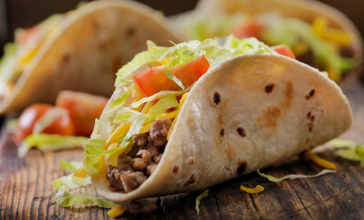 An image of taco's. A tortilla filled with mince, lettuce, cheese and tomato.