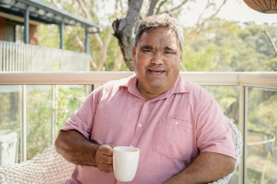 Image of smiling elderly Aboriginal man sitting outside at a table with a hot drink.