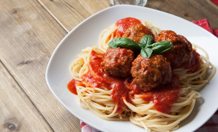 Four Italian meatballs on a bed of pasta and tomato based sauce, Plated and read to eat.