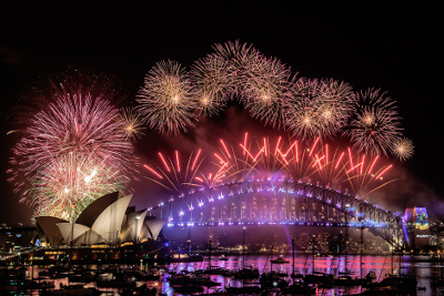 Fireworks erupting over Sydney Harbour Bridge and sails of the Sydney Opera House