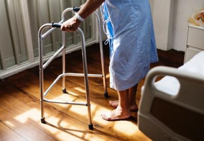 person in hospital gown using a walking frame