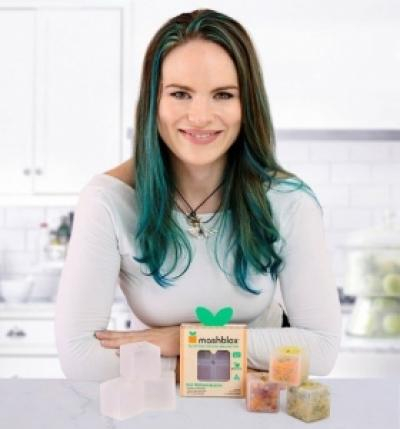 A woman with dark and green hair, smiling and sitting behind a Mashblox product display