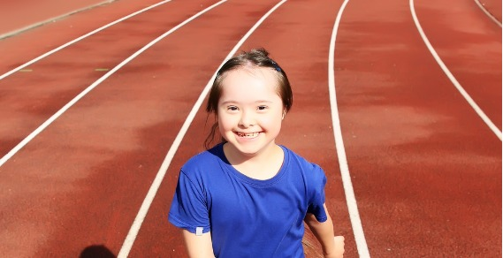 A photo of a young girl with down syndrome smiling at the camera. She is standing on an athletics track.