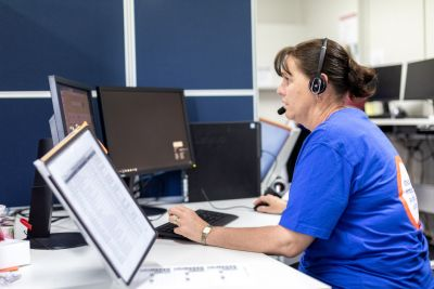 An image of an IDEAS Information Officer in a blue shirt working on a computer. She wears a headset.