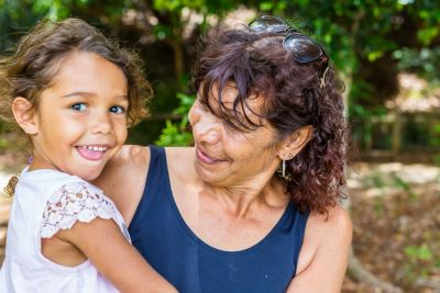 Image of smiling Aboriginal woman holding a young child in her arms.