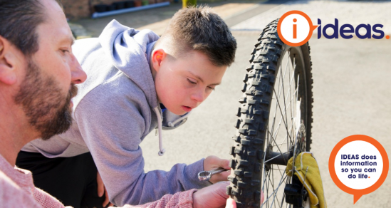 A boy with disability learns how to repair a bicycle