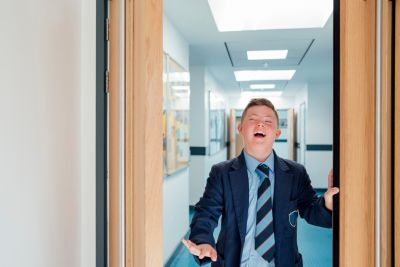 A boy in school uniform is walking though a corridor smiling.
