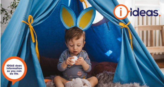 A young boy sits on a fluffy grey lambswool. He wears a pair of Easter Ears in blue and yellow, and has a grey top with hot air balloons on. He is inside a blue indoor play tent. He holds a white Easter Egg which he is looking at and in his lap is a soft toy bunny.