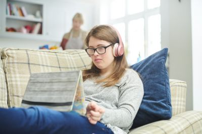 Image of a teenage girl sitting on a lounge, using an internet device, her mother is in the background