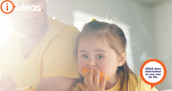 A young girl with down syndrome rests her head against an adult, the girl is eating an orange..