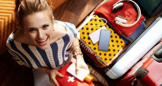 Image of a woman looking up to the camera and smiling. She is holding a first aid kit, with an open suitcase beside her.