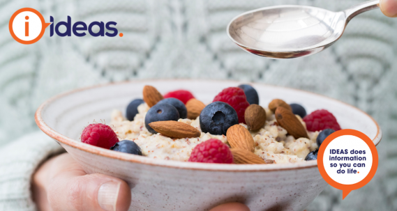 An image of a person in a light grey winter jumper. In one hand they hold a speckled bowl, inside the bowl is porridge, topped with raspberries, blueberries and almonds. In the other hand they hold a silver spoon over the bowl.