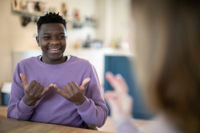 A photo of a teenage boy communicating in sign language with another person who is out of focus to the right of the image.