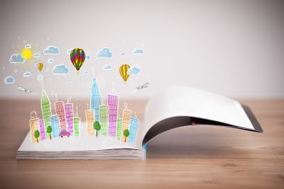 An open book with imagery of a city drawn coming out of the pages, bringing them to life