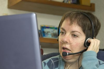 A woman with oxygen tubes and headset looking at a computer.