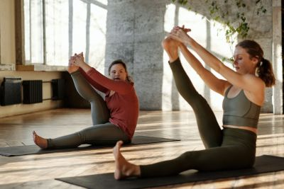 Two women, one with visible disability, stretching in a yoga pose
