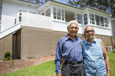 Image of elderly couple smiling with their arms around each other and standing in front of a house.