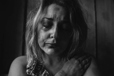 A black and white image of a woman with tears falling down her face