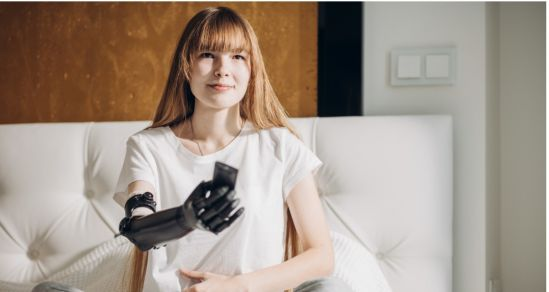 A young woman with long hair, a smile and a prosthetic arm is holding a TV remote and pointing it.
