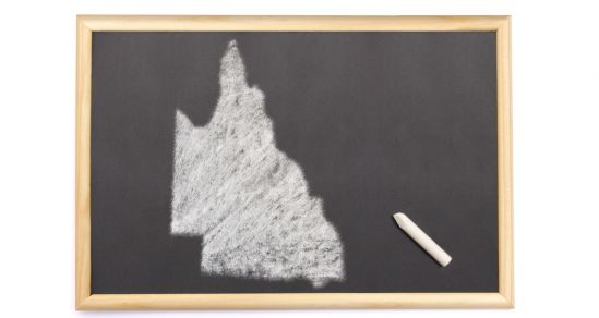 A blackboard with the shape of Queensland state drawn on it. A piece of white chalk lays to the side.