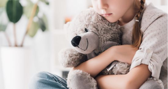 A young girl with a plait in her hair and a thoughtful look on her face is hugging a teddy bear. The teddy is smiling.