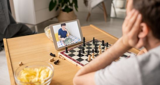 A boy sits with a chess board and ipad in front of him. A bowl of chips is to the side. On the ipad is a friend he is playing against, who also has a chessboard that we can see in the picture.