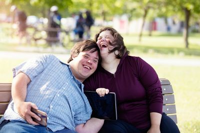 two people with disability sitting on a park bench cuddling
